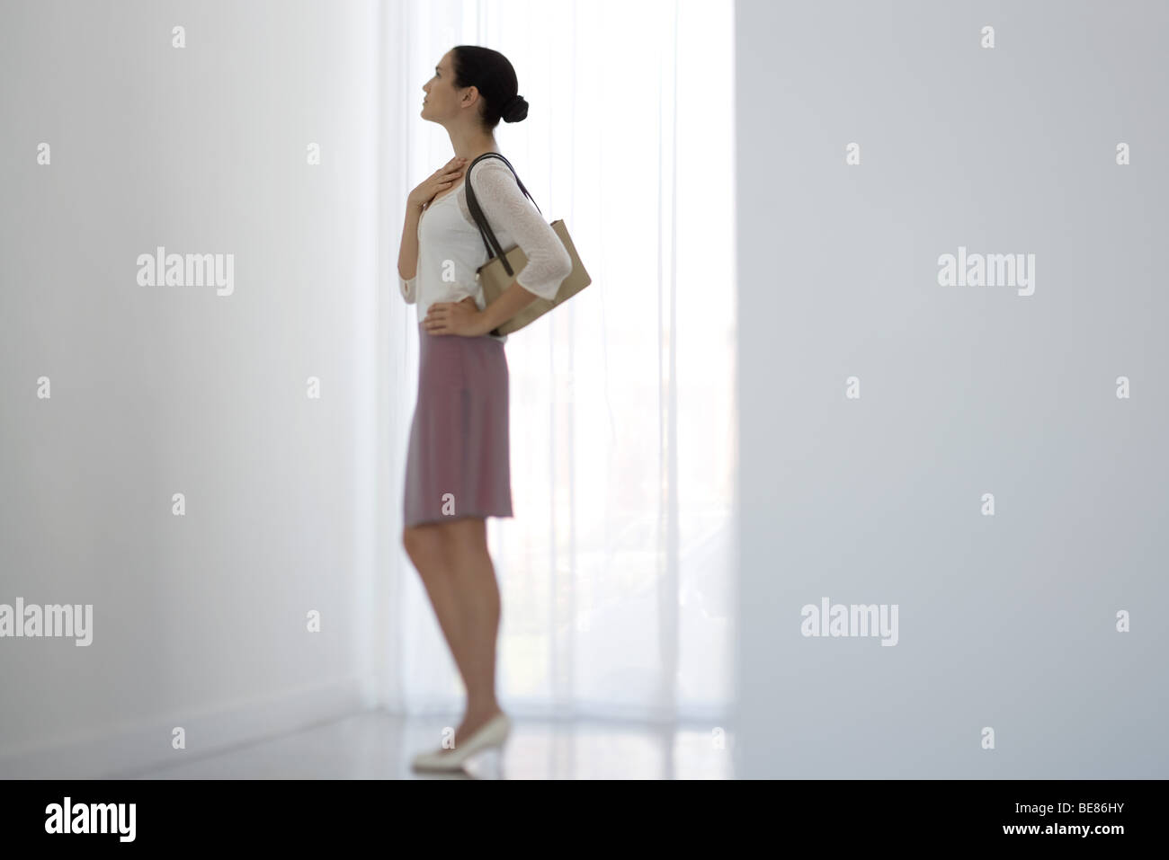 Woman standing beside window, looking up, side view - Stock Image