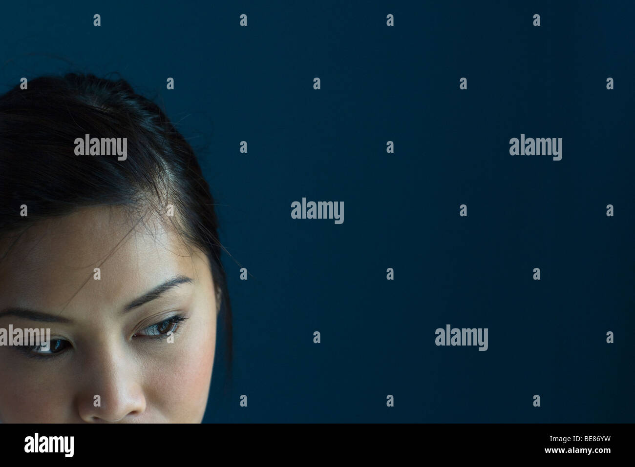 Woman looking away with sideways glance, cropped - Stock Image