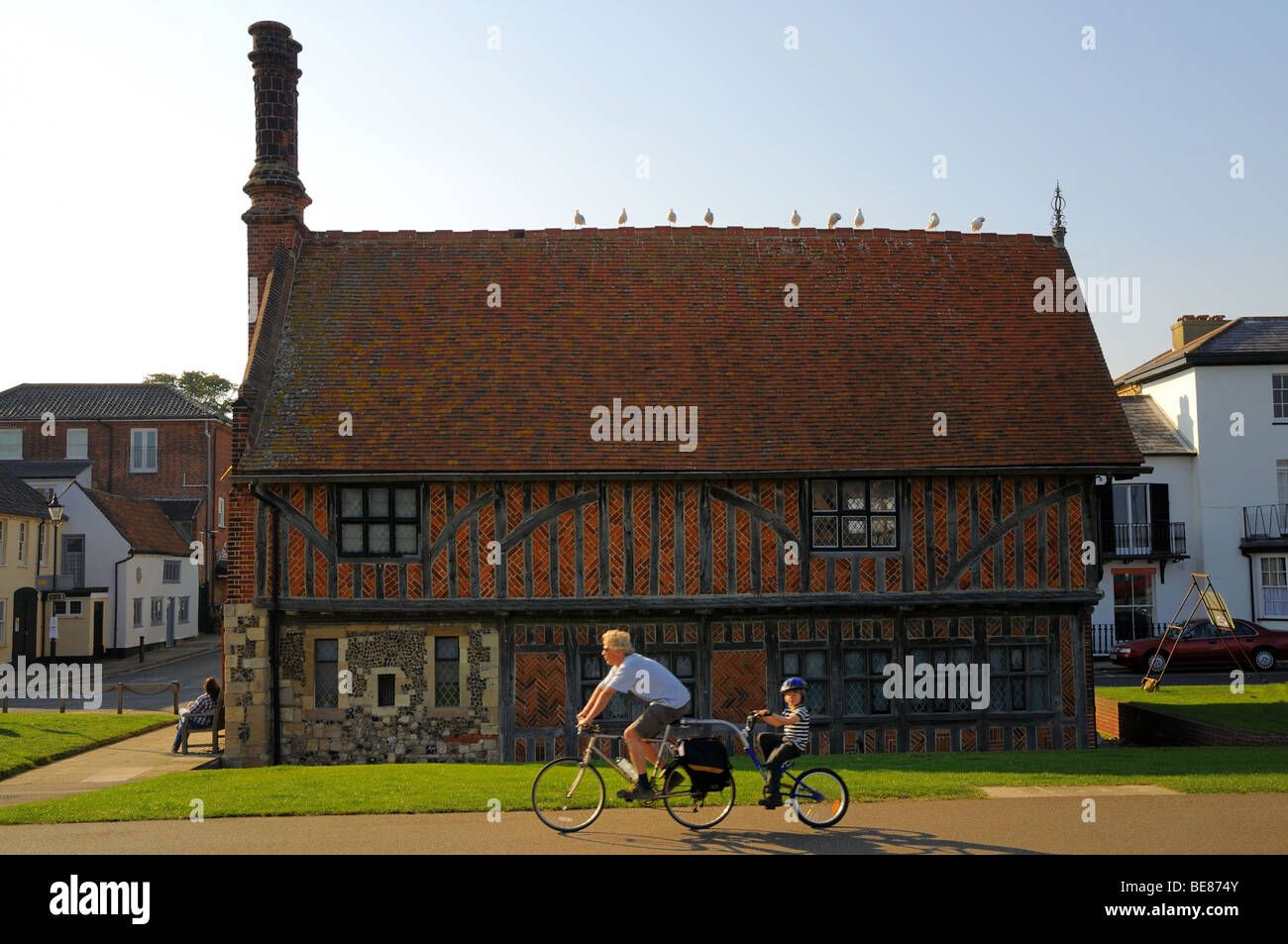 Cyclists passing by Moot Hall, on promenade. Moot Hall is now a Museum. Aldeburgh Suffolk - Stock Image