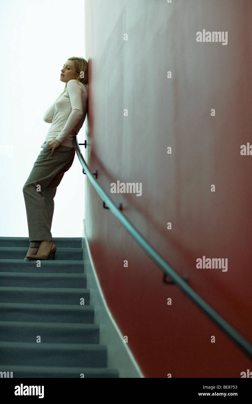 Woman standing at top of stairs, leaning against wall, looking away - Stock Image