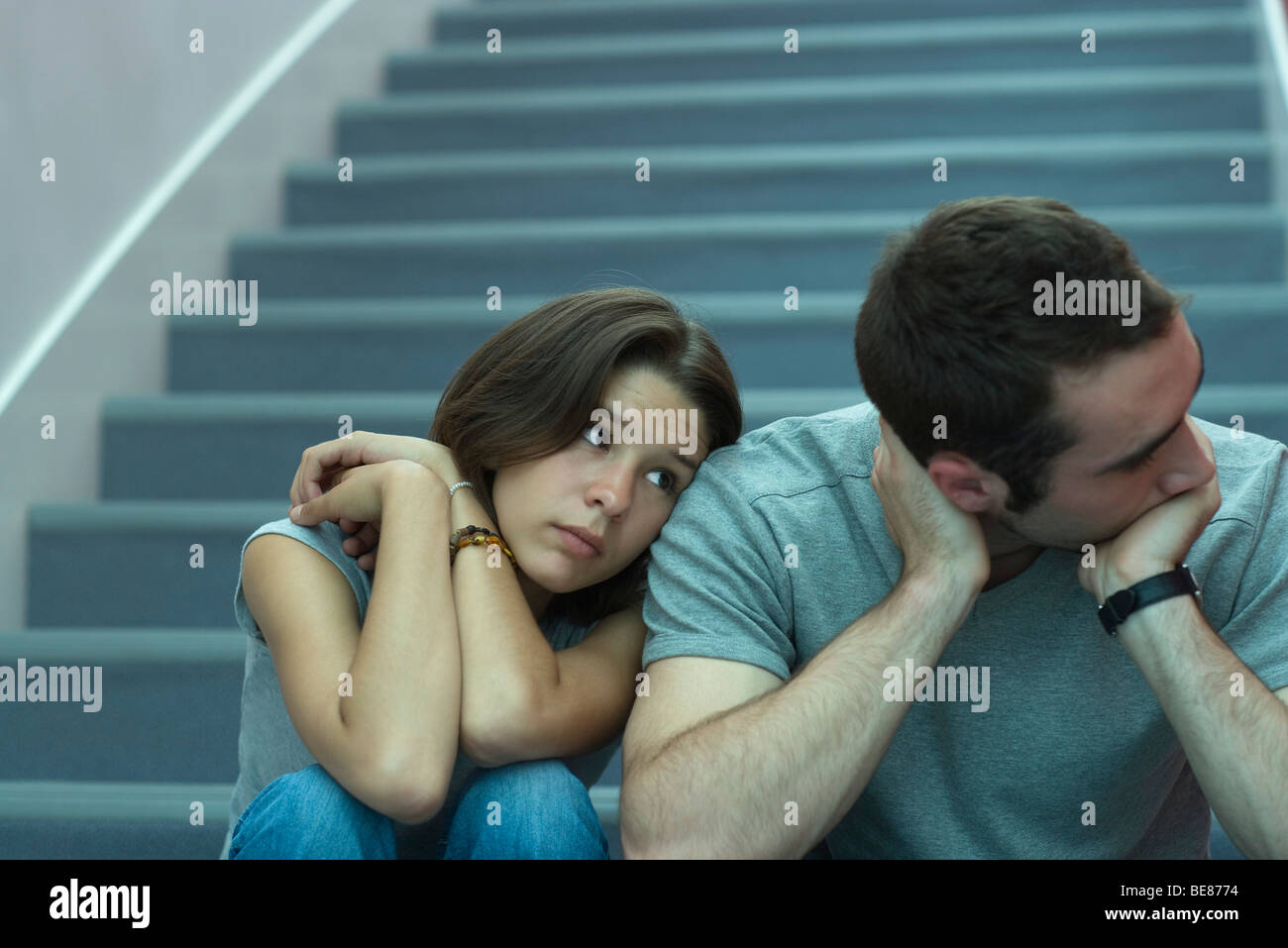 Young couple sitting side by side on stairs, woman leaning head on man's shoulder, man looking away - Stock Image