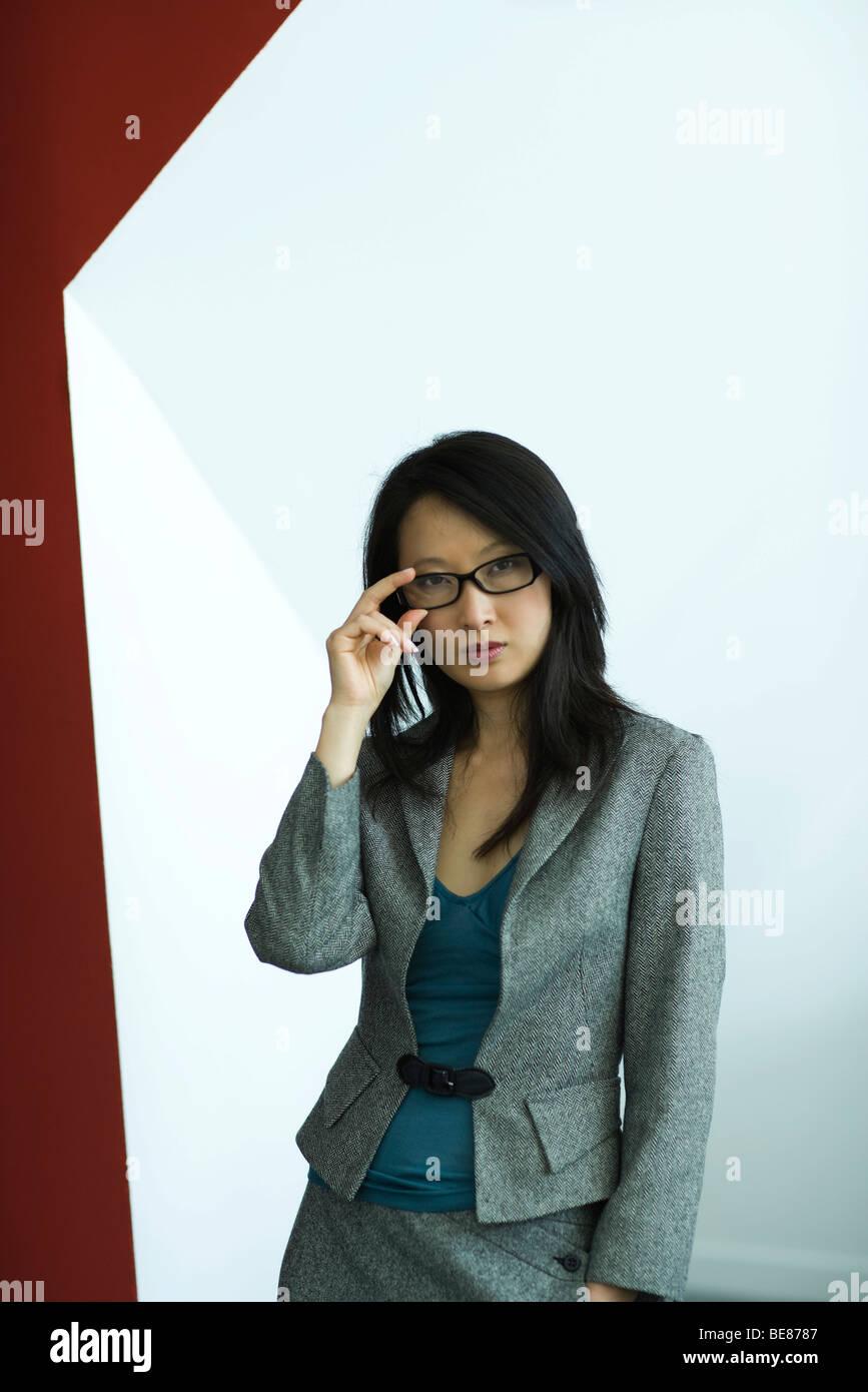 Businesswoman adjusting glasses, portrait - Stock Image