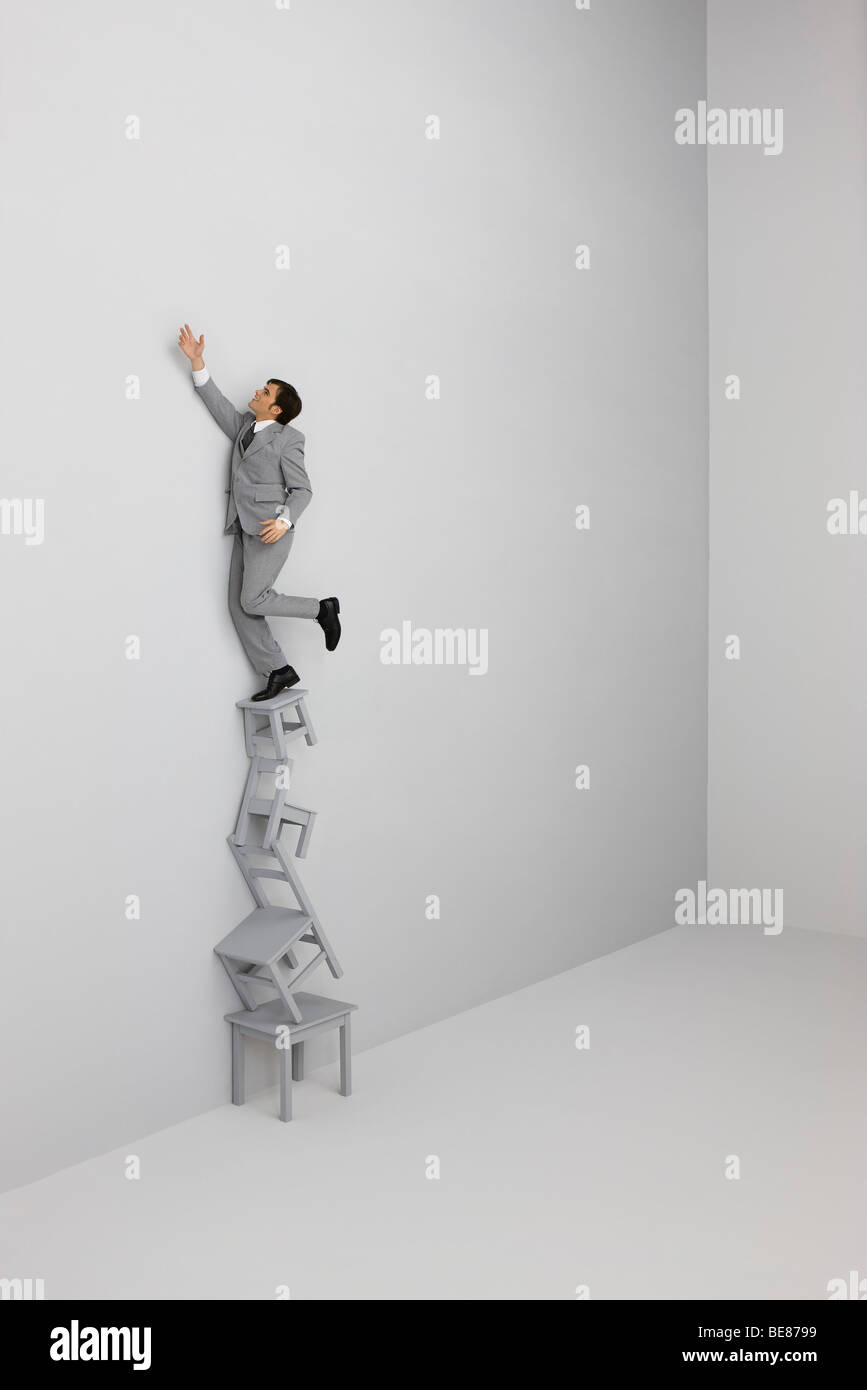 Businessman standing on top of stack of chairs - Stock Image