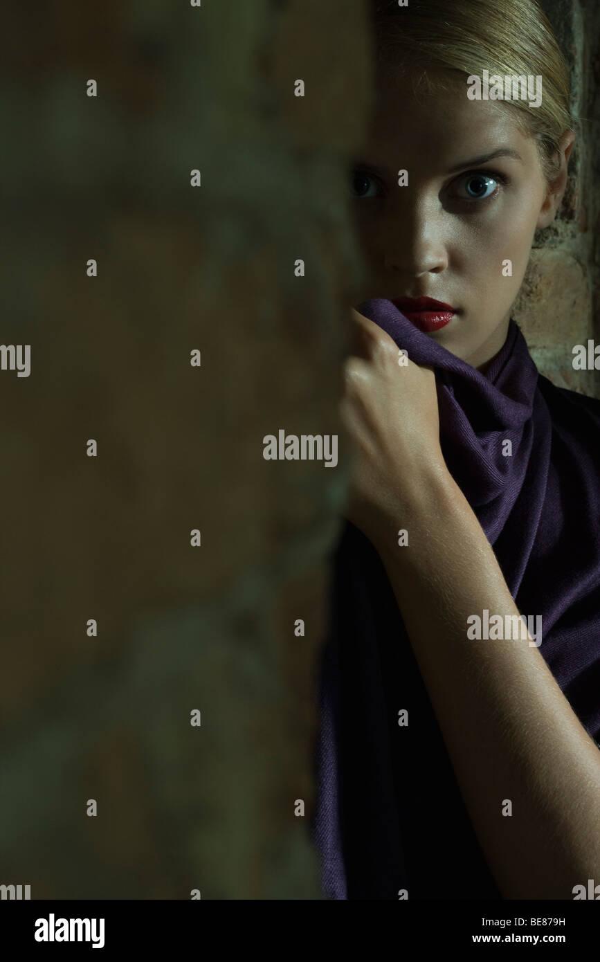 Woman hiding behind brick wall, staring at camera with wide eyes - Stock Image