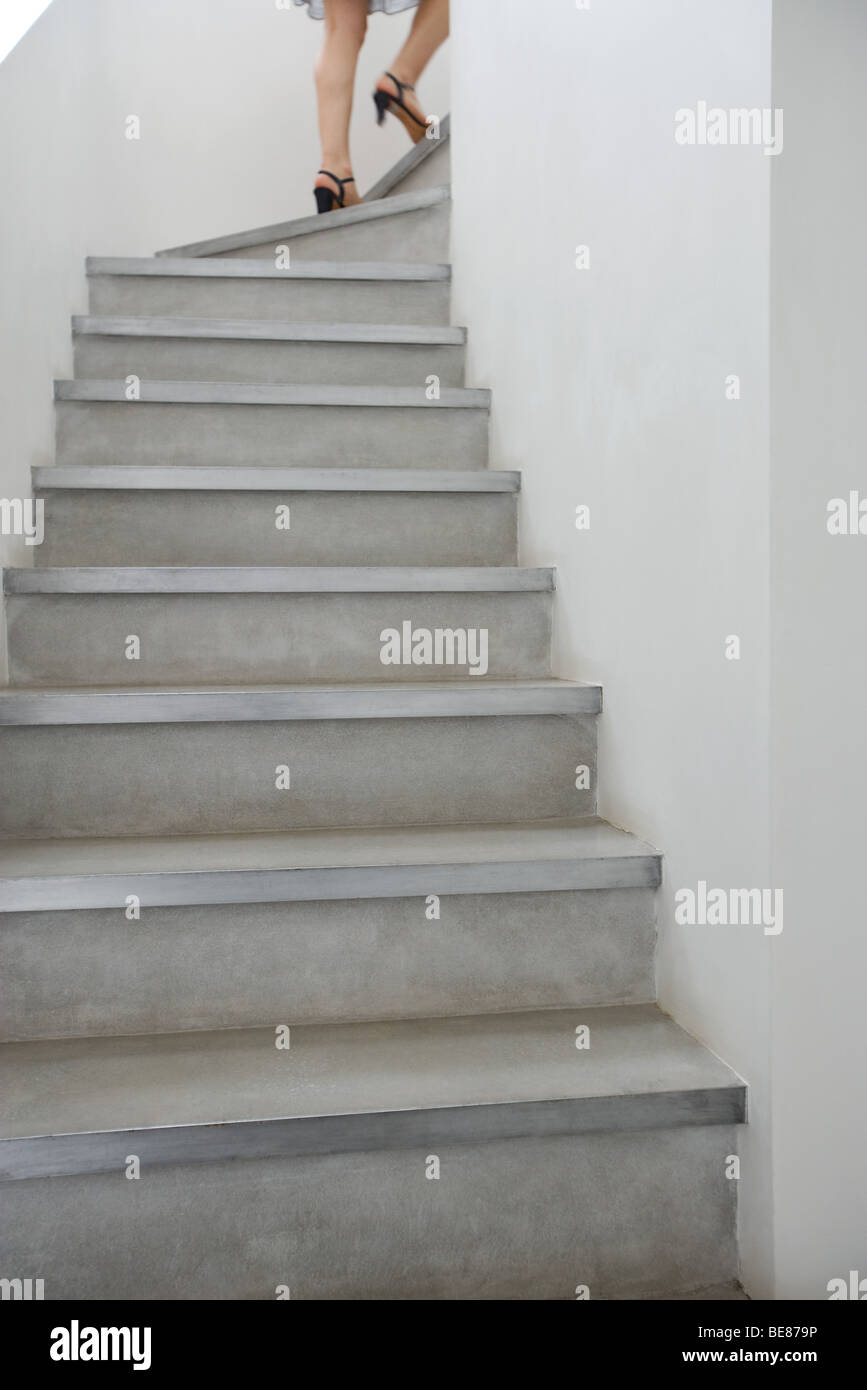 Woman walking up staircase, cropped, low angle view - Stock Image