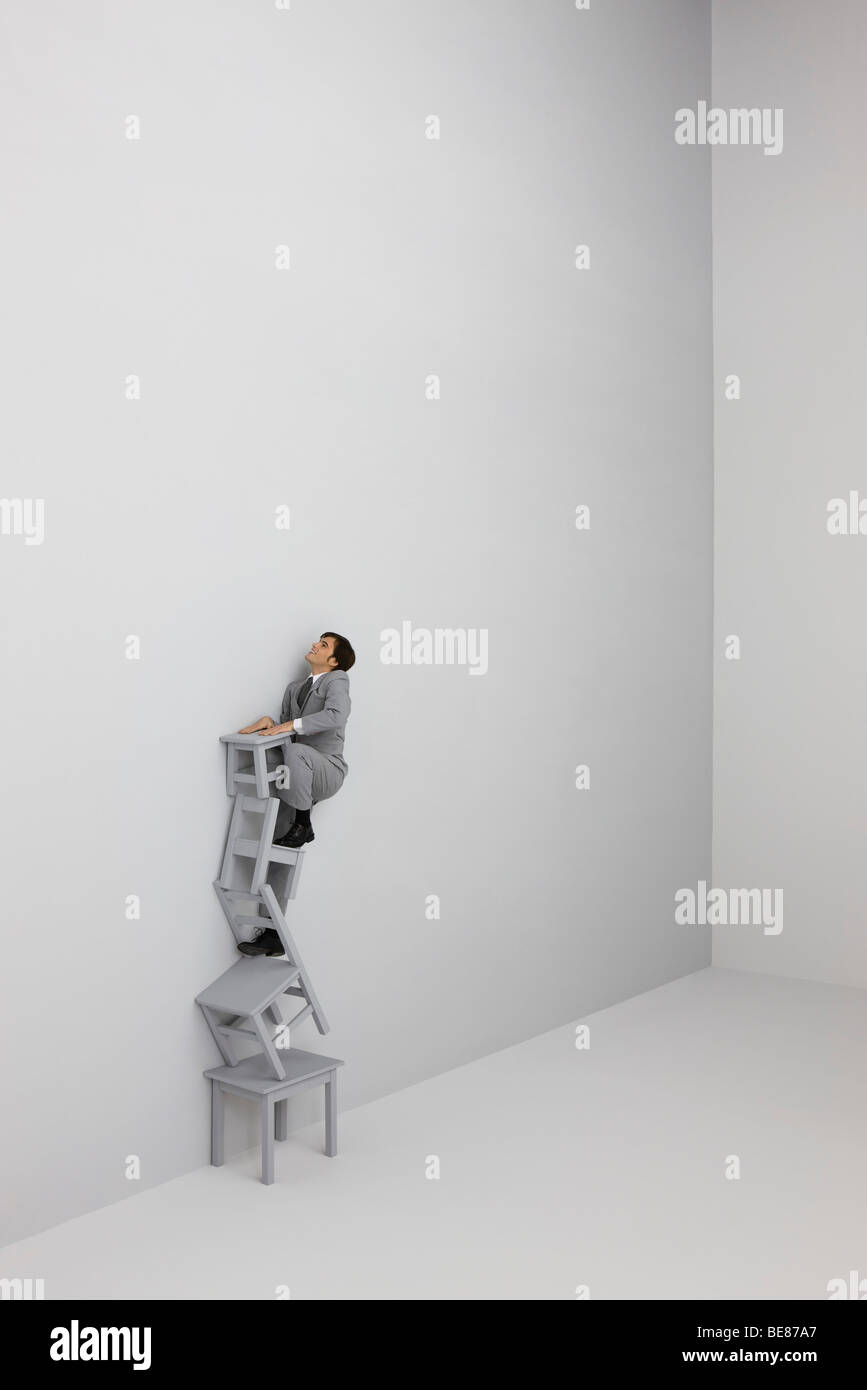 Businessman climbing ladder made of stacked chairs - Stock Image