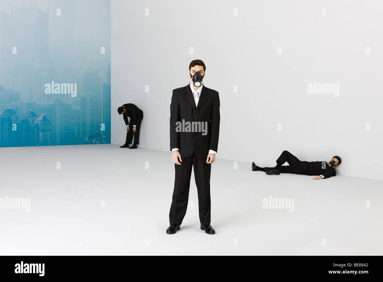 Businessmen wearing gas mask, cityscape obscured by smog in background - Stock Image