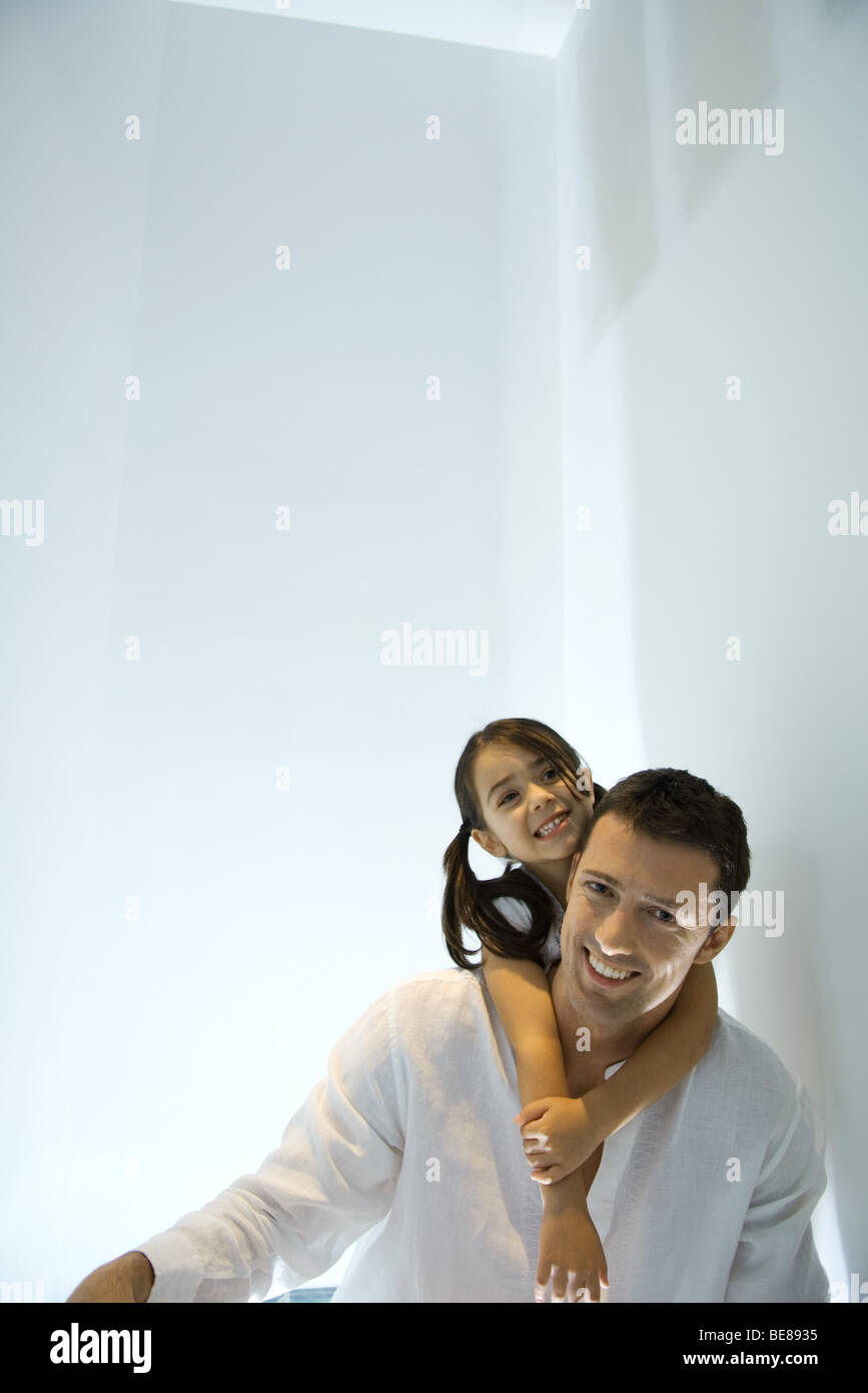 Little girl with arms around father's neck, both smiling - Stock Image