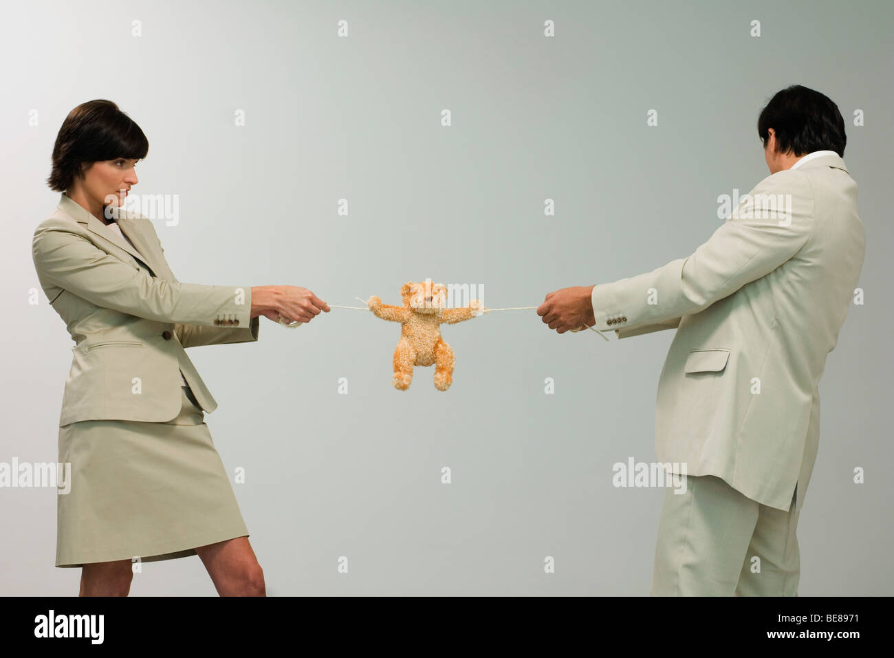 Professional couple playing tug of war with teddy bear - Stock Image