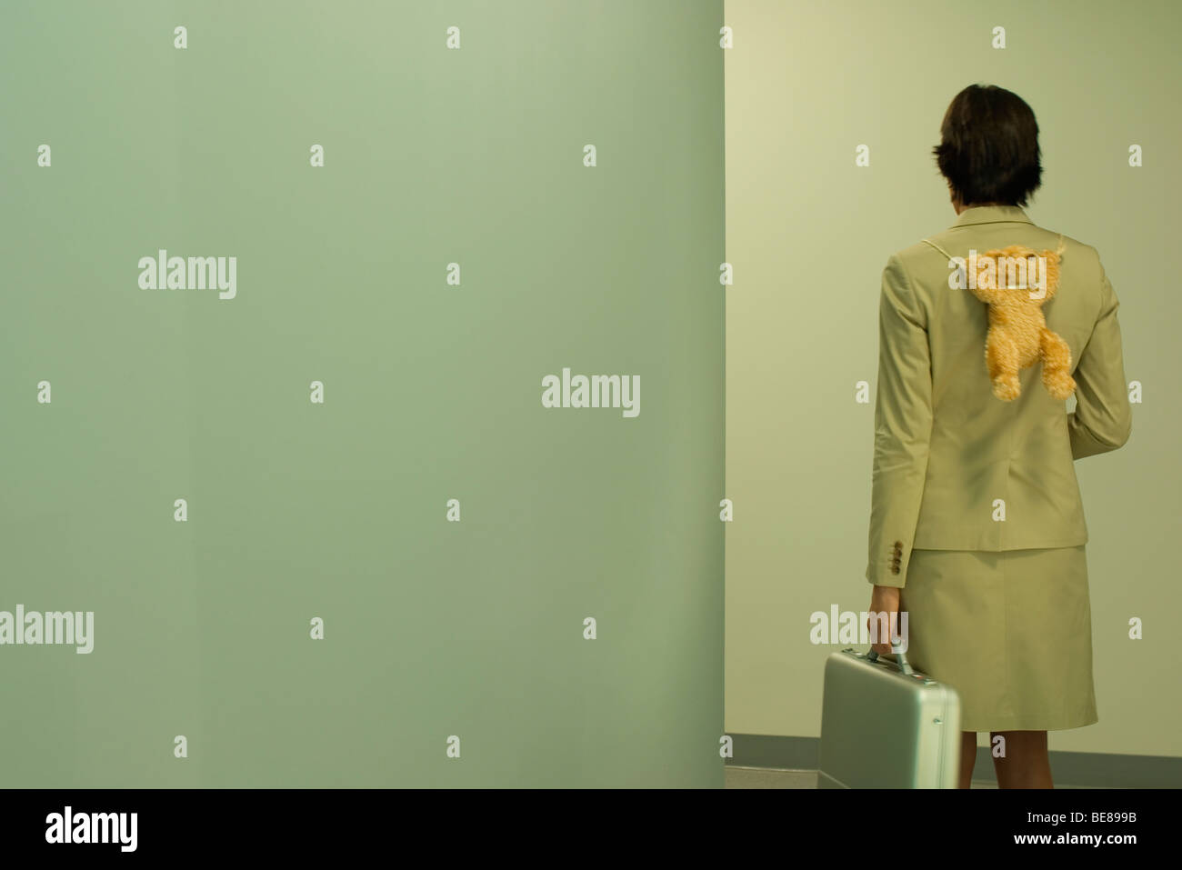 Businesswoman with briefcase carrying teddy bear on back - Stock Image