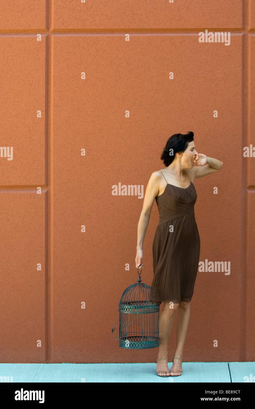 Woman standing on sidewalk yawning, holding empty birdcage - Stock Image