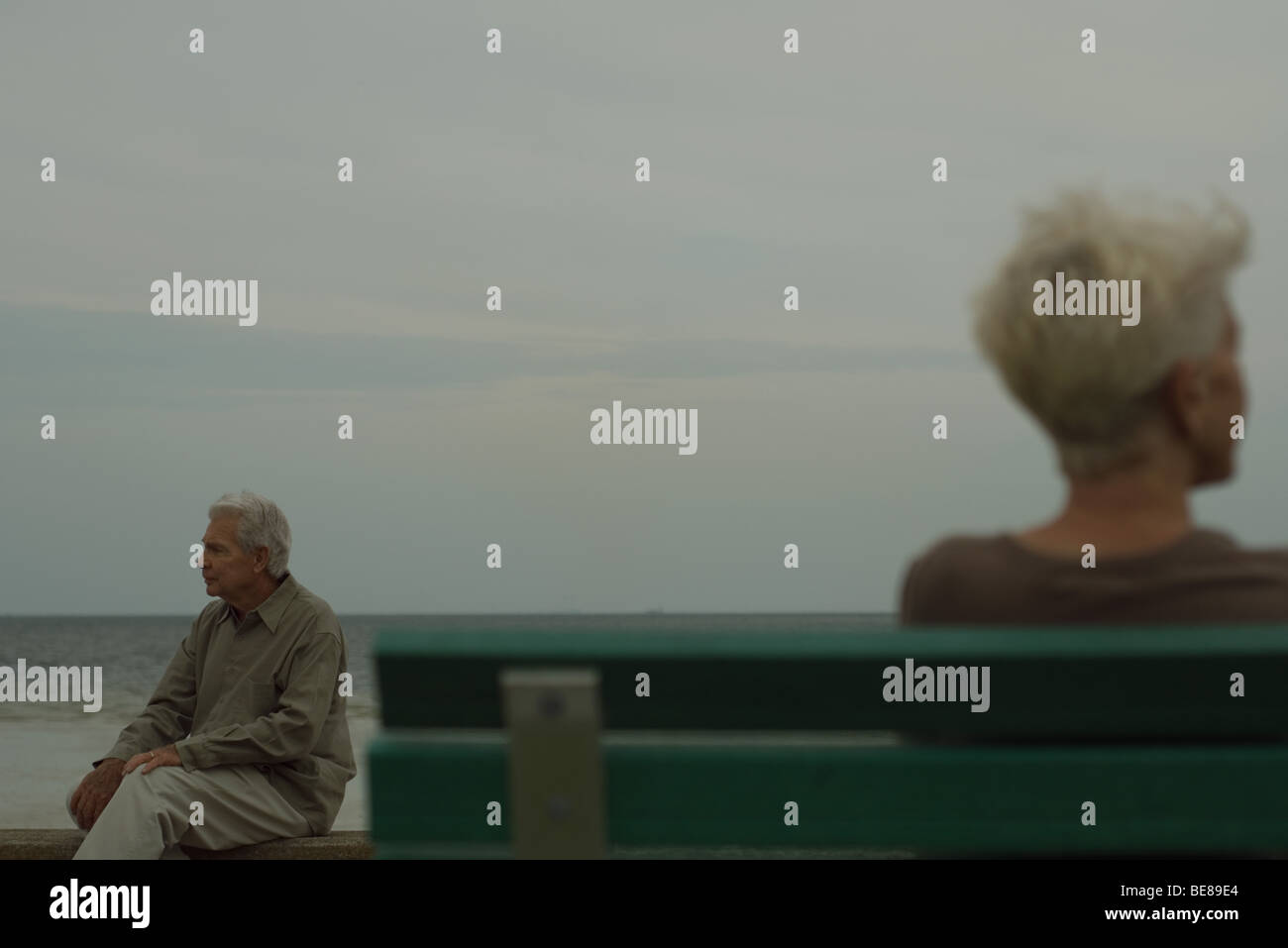 Senior man sitting on bench, looking away, senior woman in foreground - Stock Image