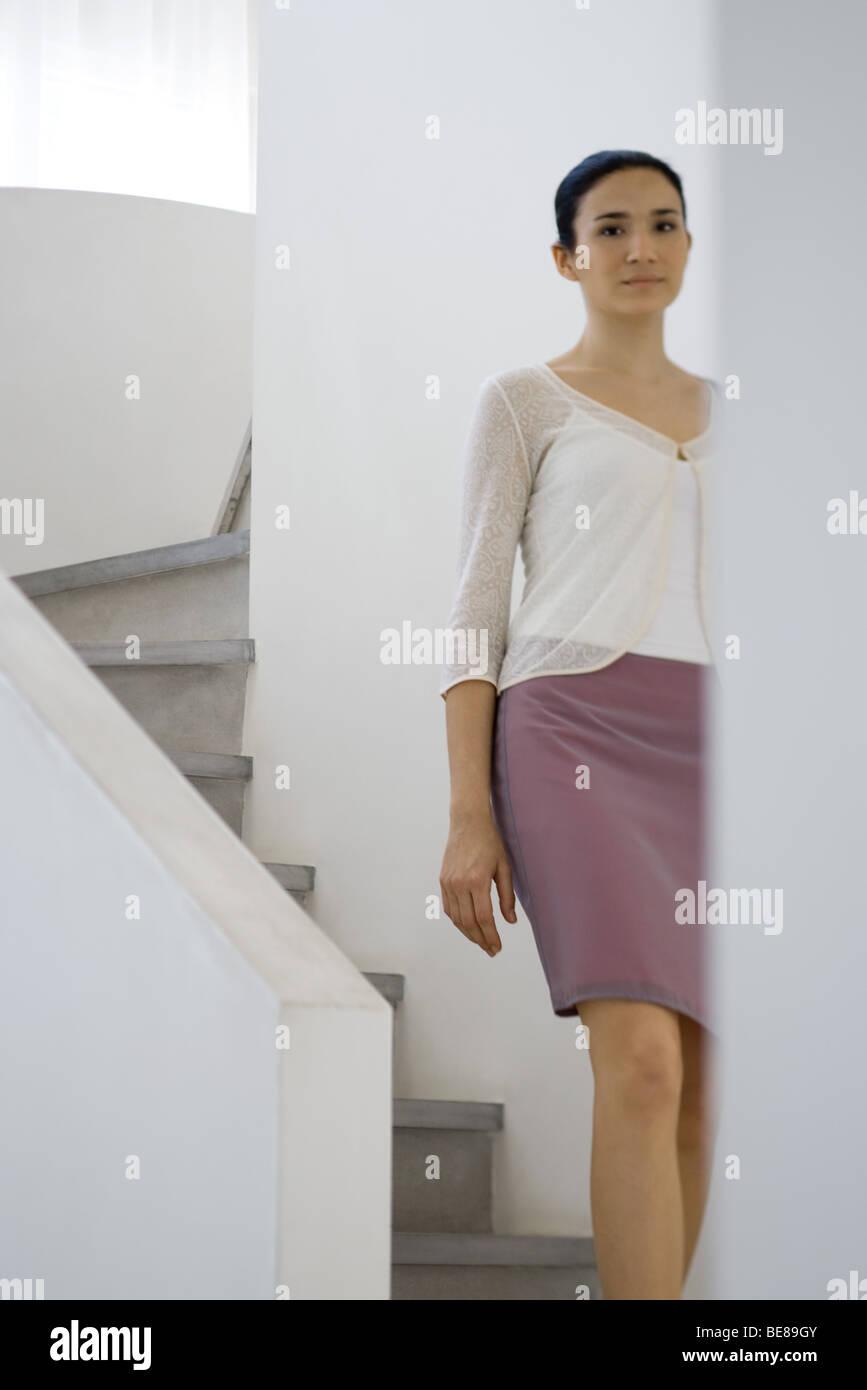 Woman walking down steps, looking at camera - Stock Image