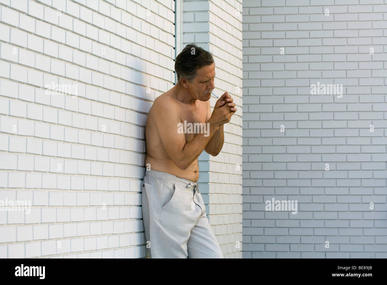 Bare-chested man leaning against wall lighting cigarette - Stock Image