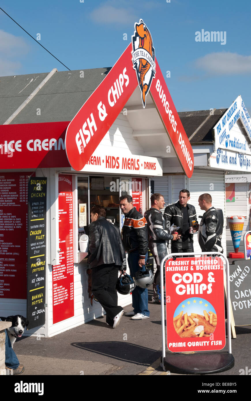 Fish and chips and fast food huts on the quayside at West Bay Dorset - Stock Image