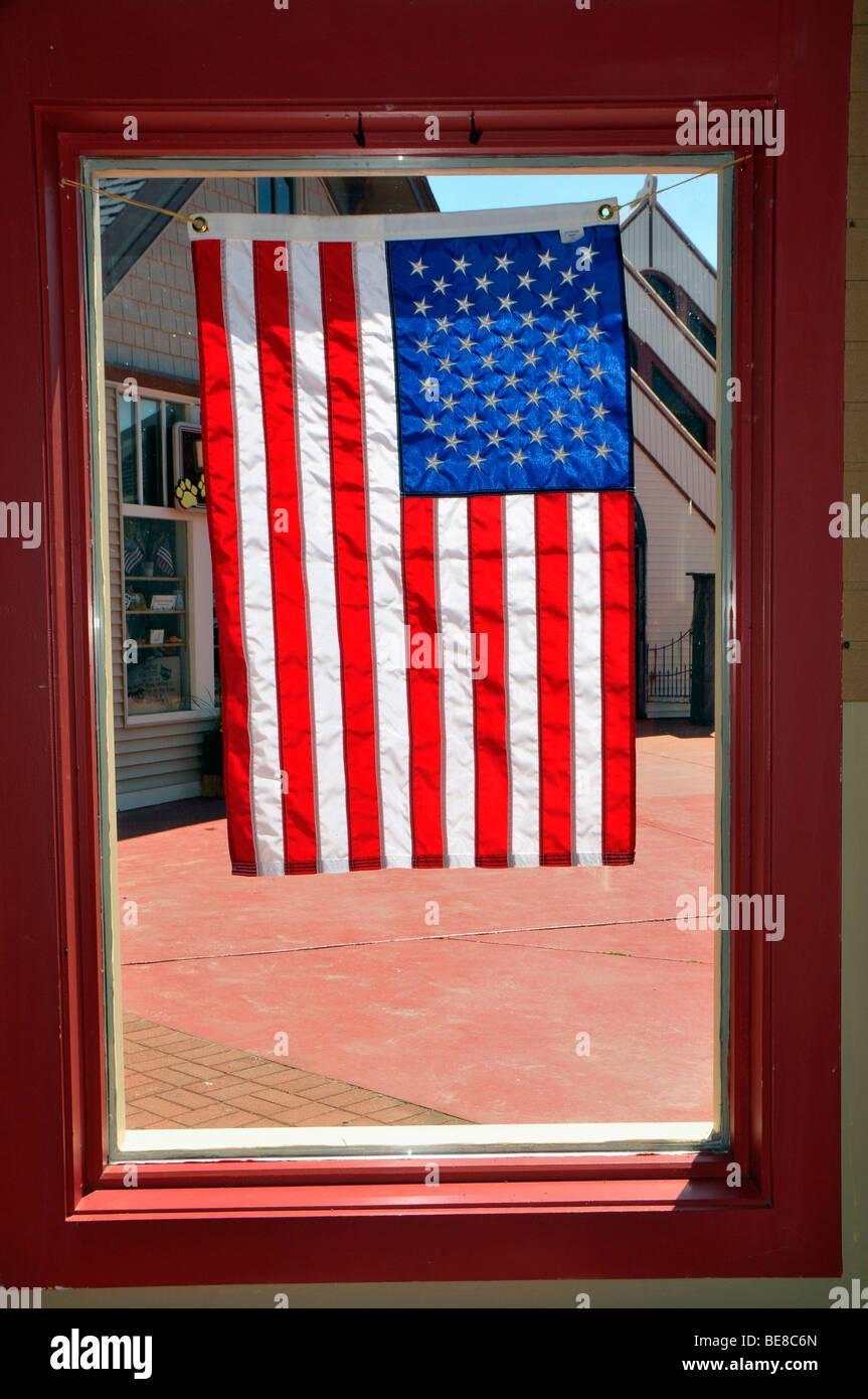 U.S. Flag in window Mackinaw City Michigan - Stock Image