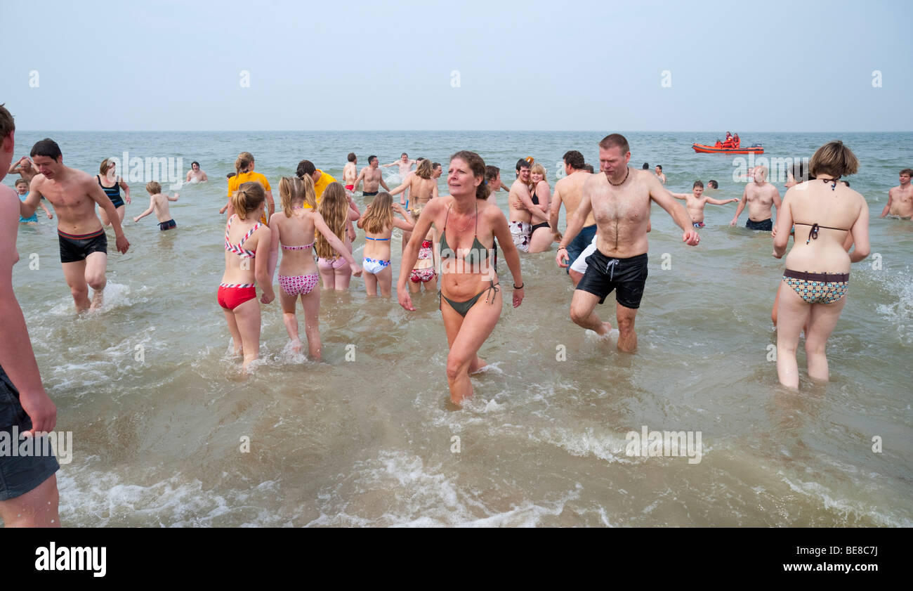 Vacationists in swimwear stand in the North Sea in cool weather at the traditional Renesse Easter Paasduik (Easter - Stock Image