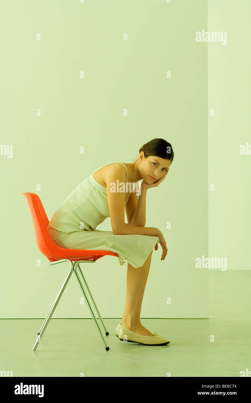 Woman sitting in chair, leaning on elbow, looking at camera - Stock Image