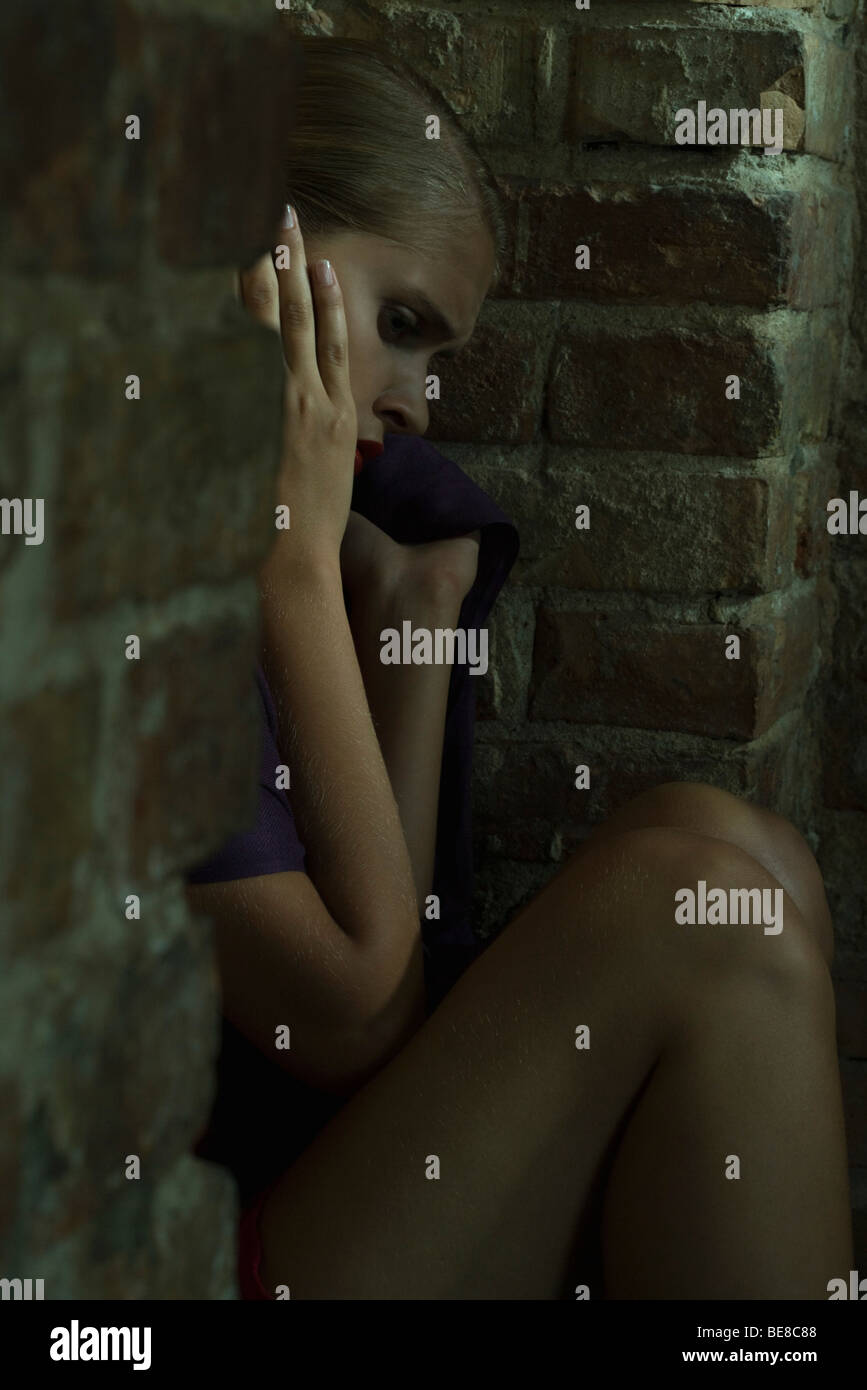 Woman sitting on ground leaning against brick wall, holding head, looking down - Stock Image