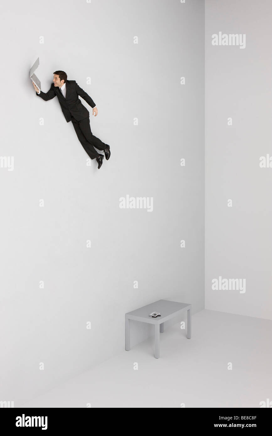 Businessman holding laptop computer flying away from desk below - Stock Image