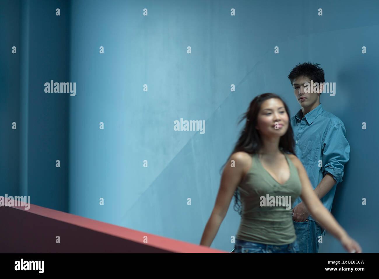 Young woman walking down corridor smiling, man watching as she walks by - Stock Image