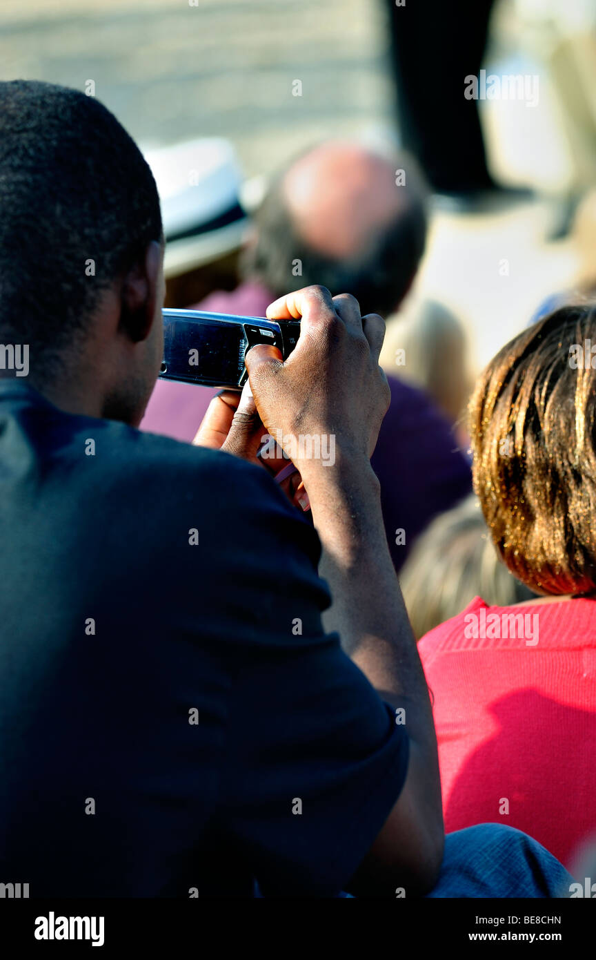 Paris, France - Black Man Taking Photos with Cellphone at Public Event - Stock Image
