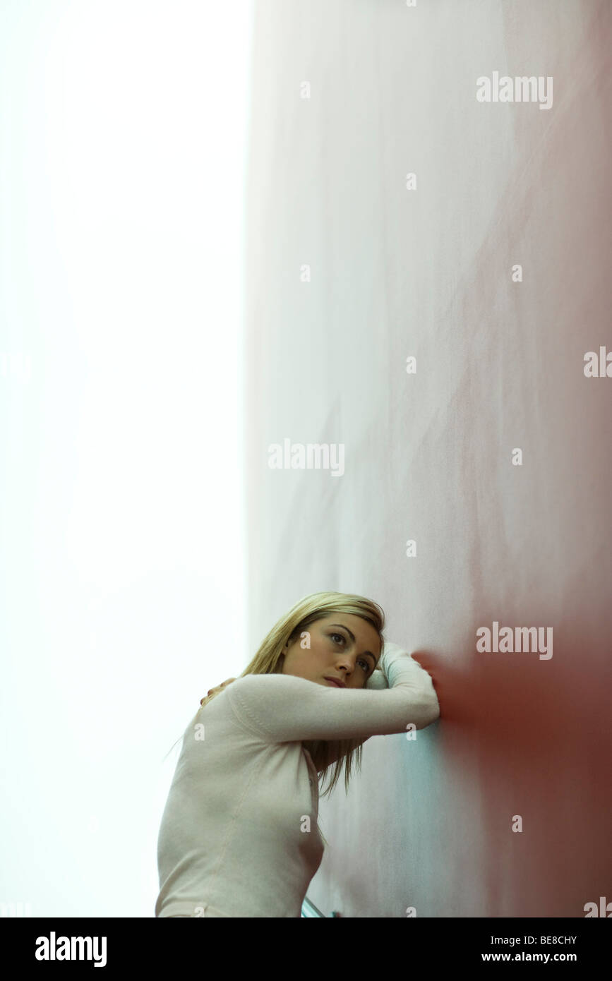 Woman leaning against wall, resting head on arms - Stock Image
