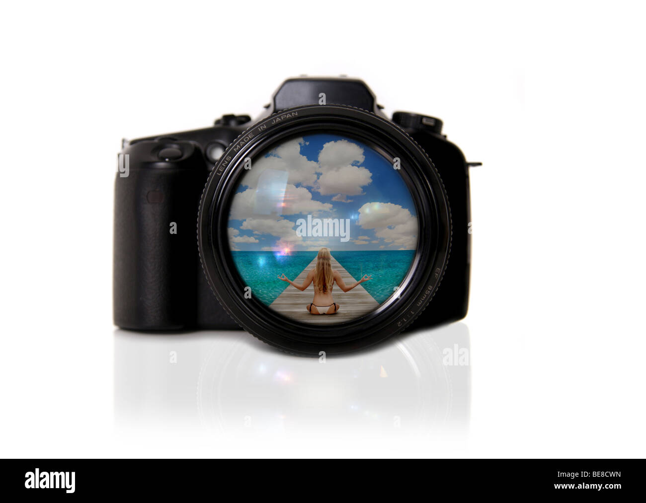 Camera Isolated With Reflected Image of the Beach in the Lens - Stock Image