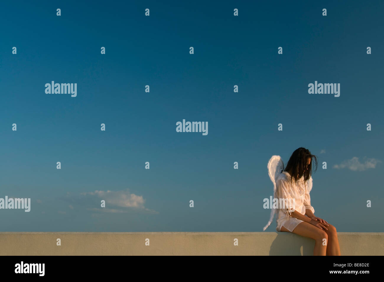 Woman wearing angel wings sitting on ledge, head down, hair obscuring face - Stock Image