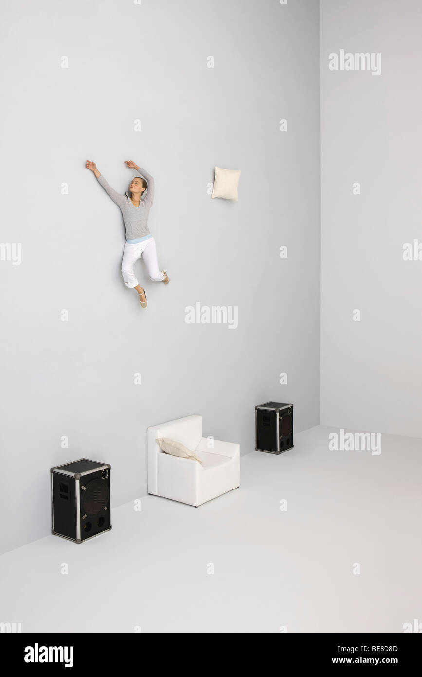Woman with arms raised floating midair above armchair - Stock Image