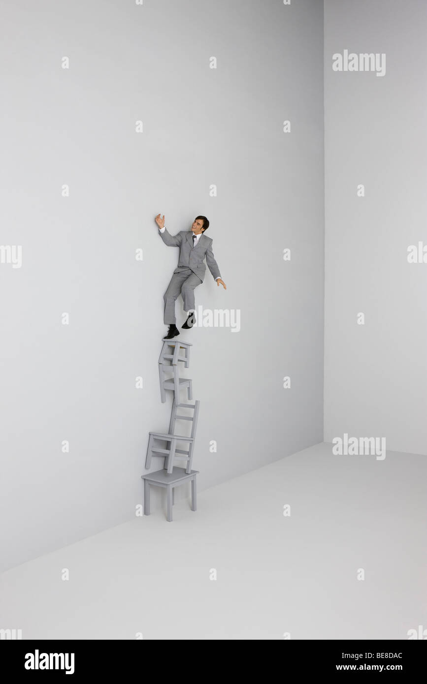 Businessman balanced on top of precarious stack of chairs - Stock Image