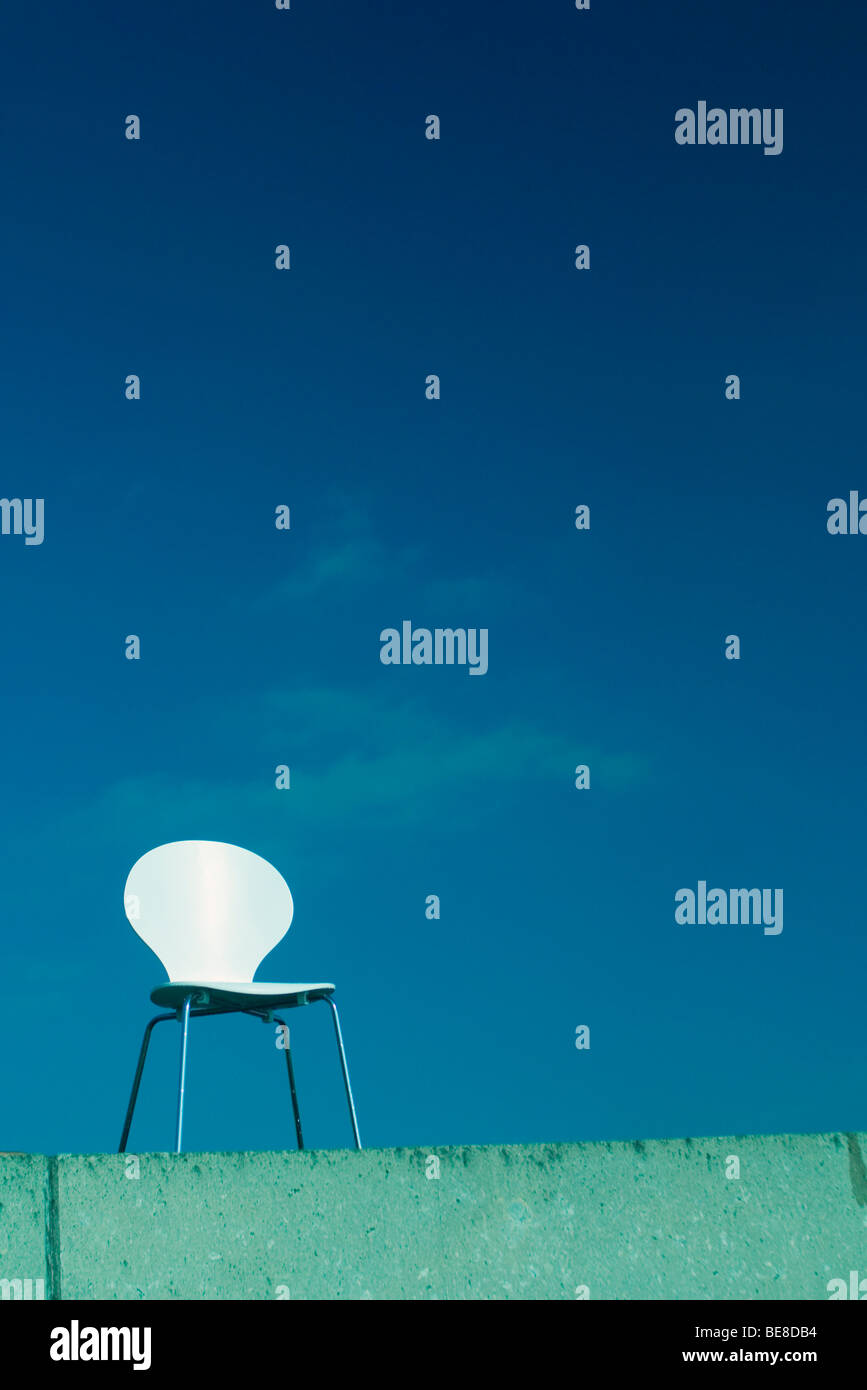 Chair set on ledge against blue sky, low angle view - Stock Image