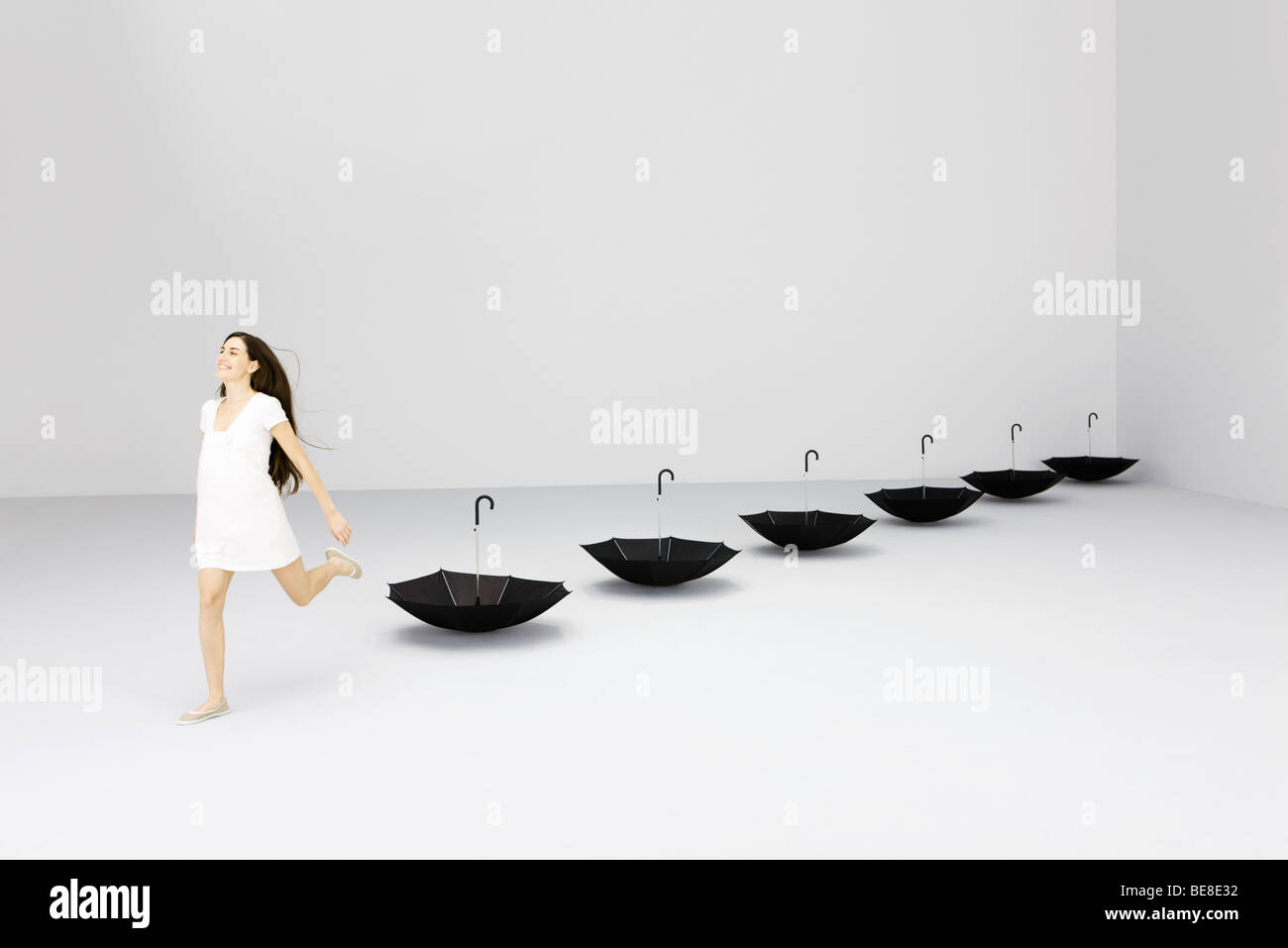 Woman running, upside down umbrellas lined up behind her Stock Photo