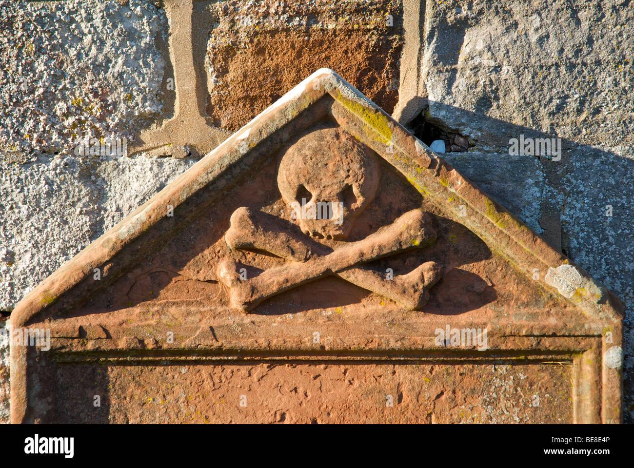 Gravestone with skull & crossbones, outside All Saints Church, Bolton, Eden, Cumbria, England UK - Stock Image