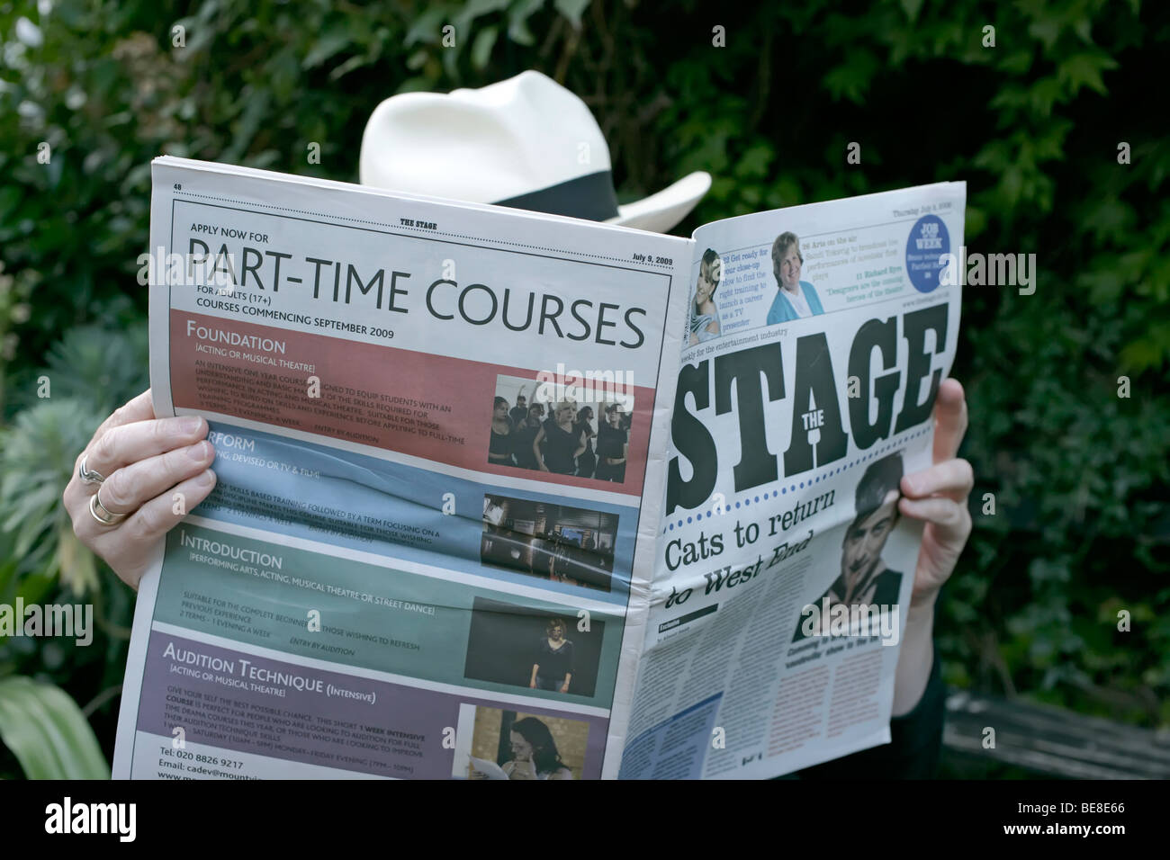 Reading the Stage Newspaper with an advert for part time courses - Stock Image