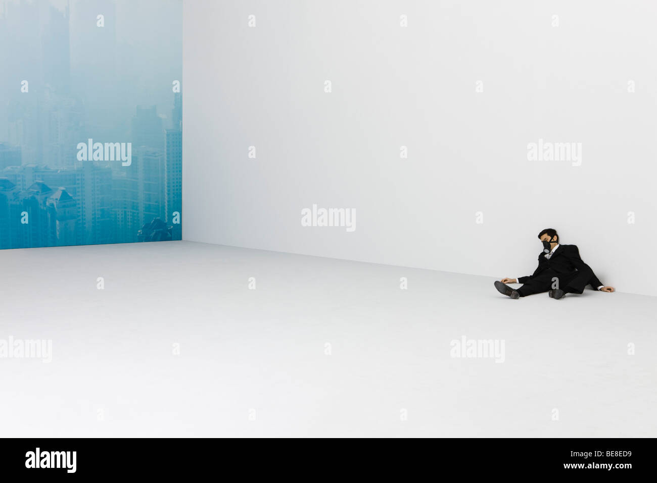 Businessman lying on floor, wearing gas mask, cityscape obscured by smog in background - Stock Image