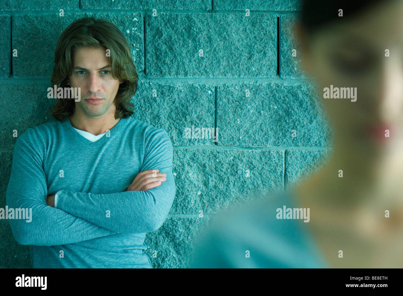 Man with folded arms and sullen expression looking at woman in foreground - Stock Image