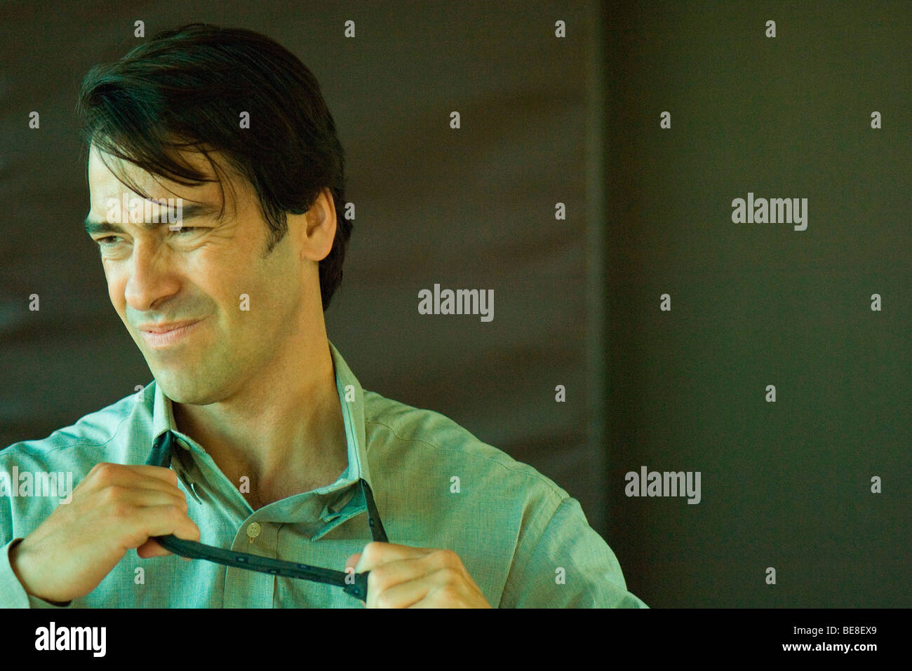 Businessman grimacing while taking off tie - Stock Image