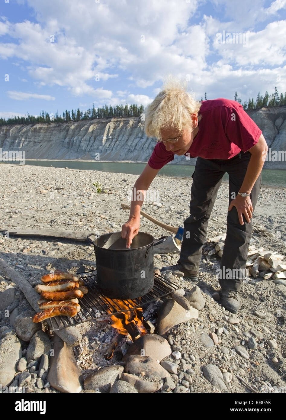 Woman cooking on a campfire, BBQ sausages, bratwurst, kettle, pot, grill, upper Liard River, Yukon Territory, Canada Stock Photo