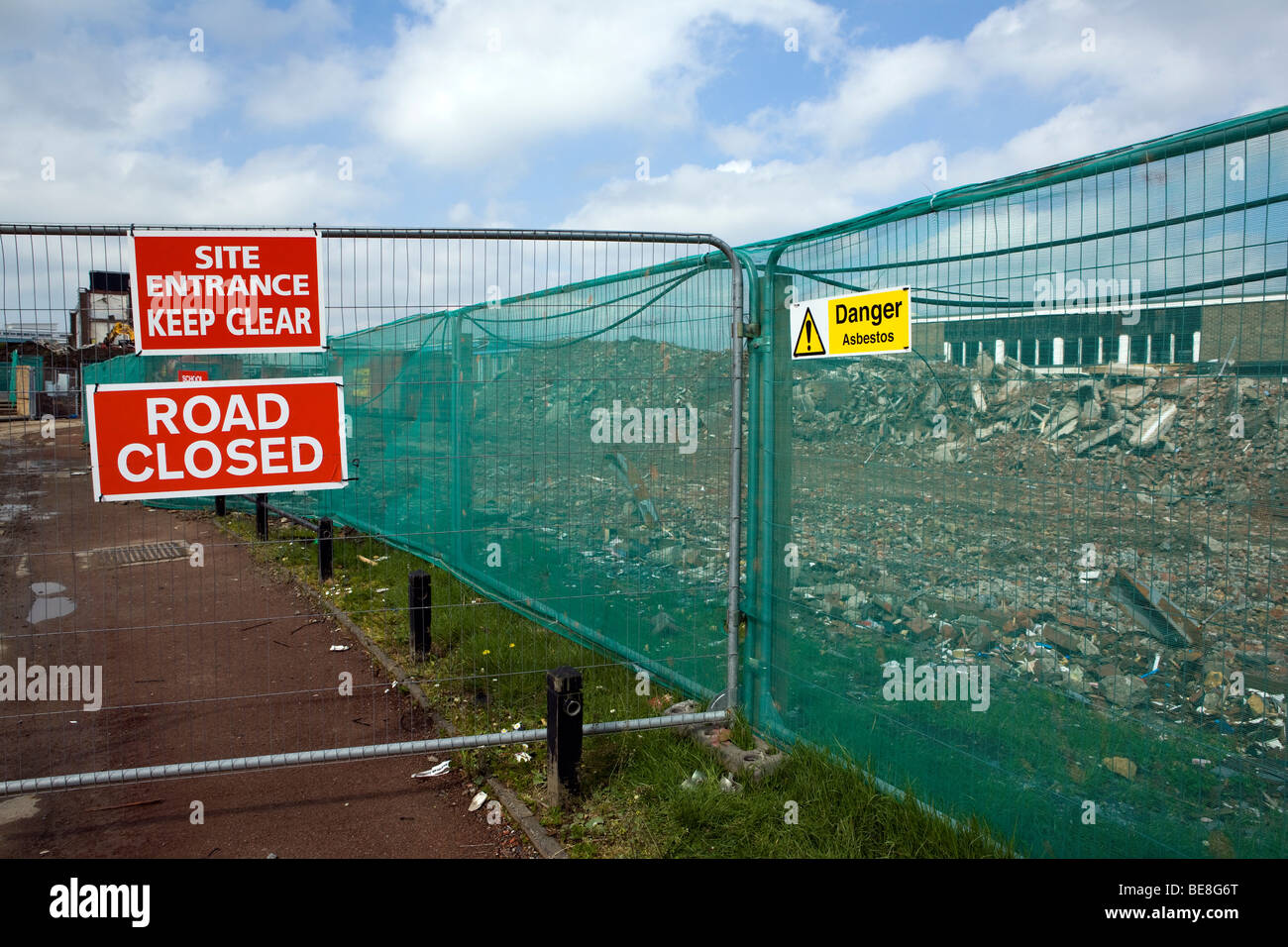 A sign warning of asbestos on a fenced off school demolition site, UK - Stock Image