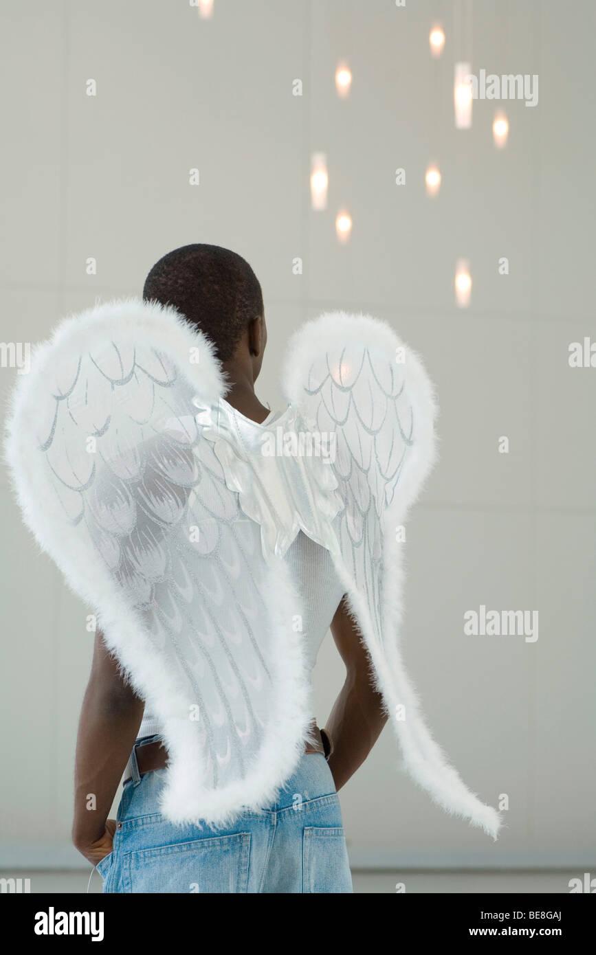 Male wearing angel wings, looking away, rear view - Stock Image