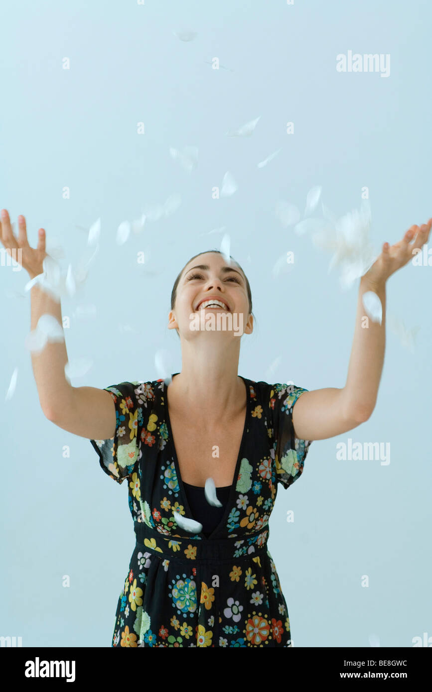 Woman tossing flower petals into air - Stock Image