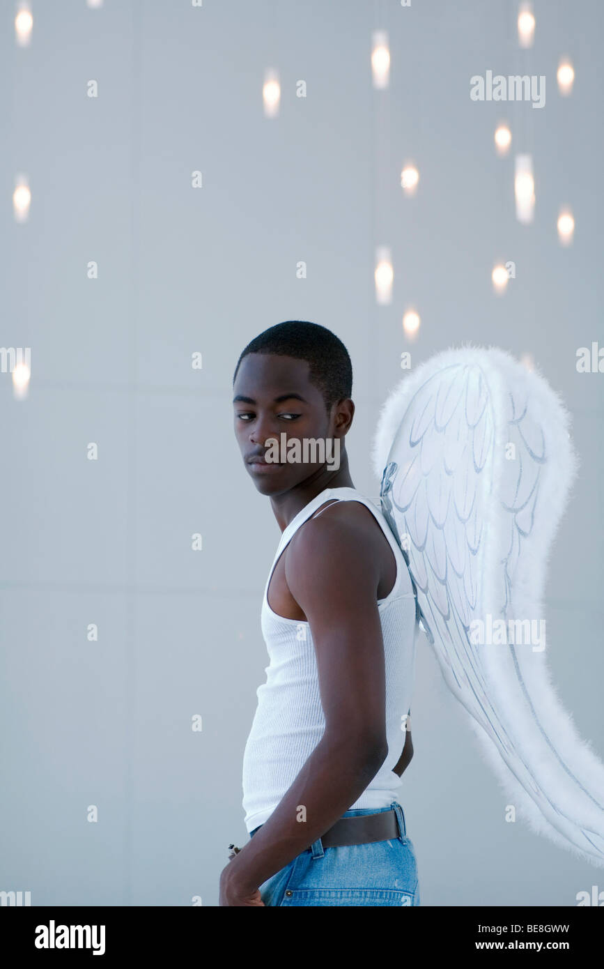 Male wearing angel wings, looking over shoulder - Stock Image