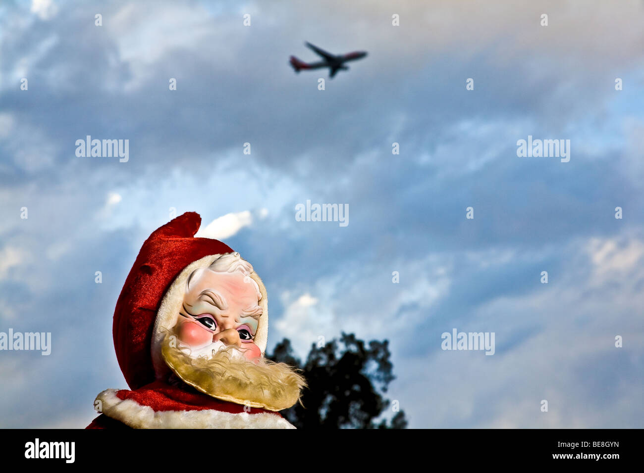 A 1960's era stuffed Santa Claus stands in the evening light as an airplane flies by overhead - Stock Image
