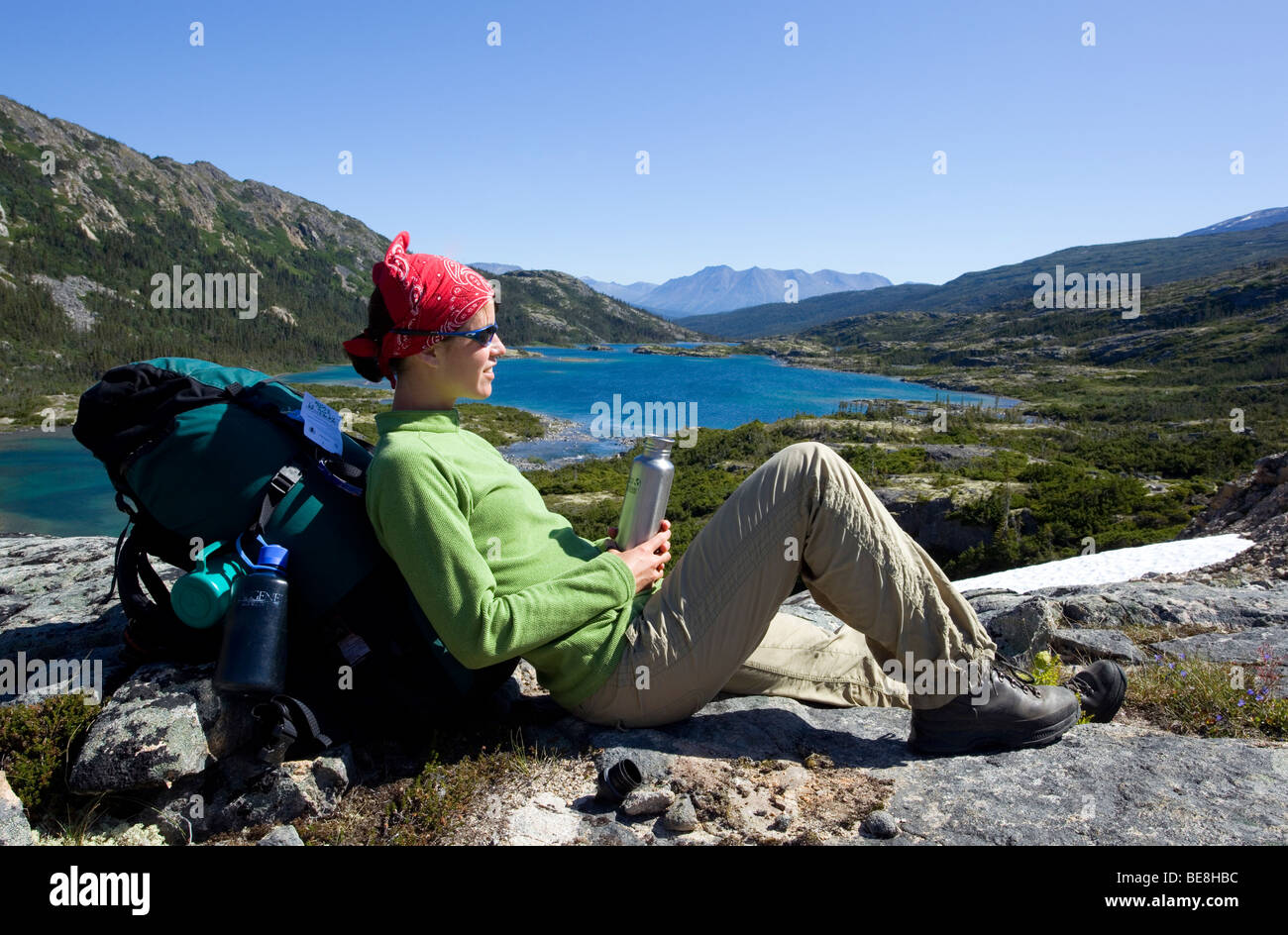 Young woman resting, hiker with backpack, water bottle, panorama, deep lake behind, historic Chilkoot Trail, Chilkoot - Stock Image