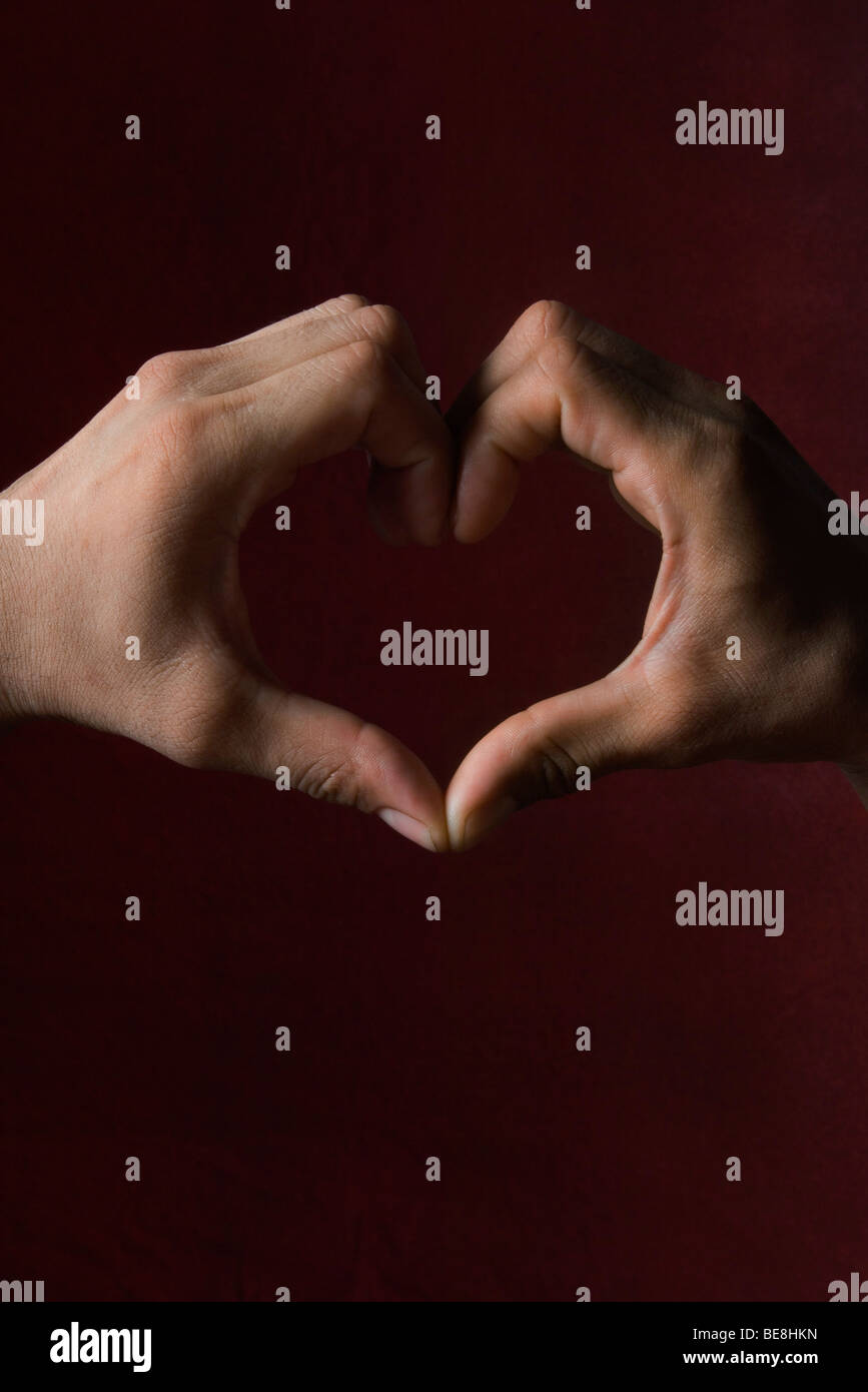 Hands together forming heart - Stock Image