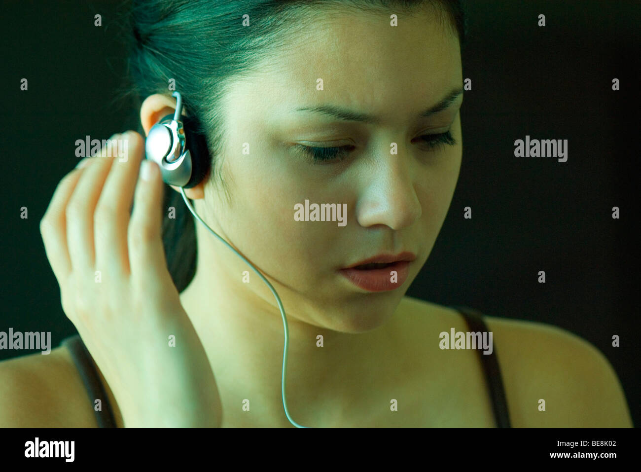 Woman listening to headphones, furrowing brow - Stock Image
