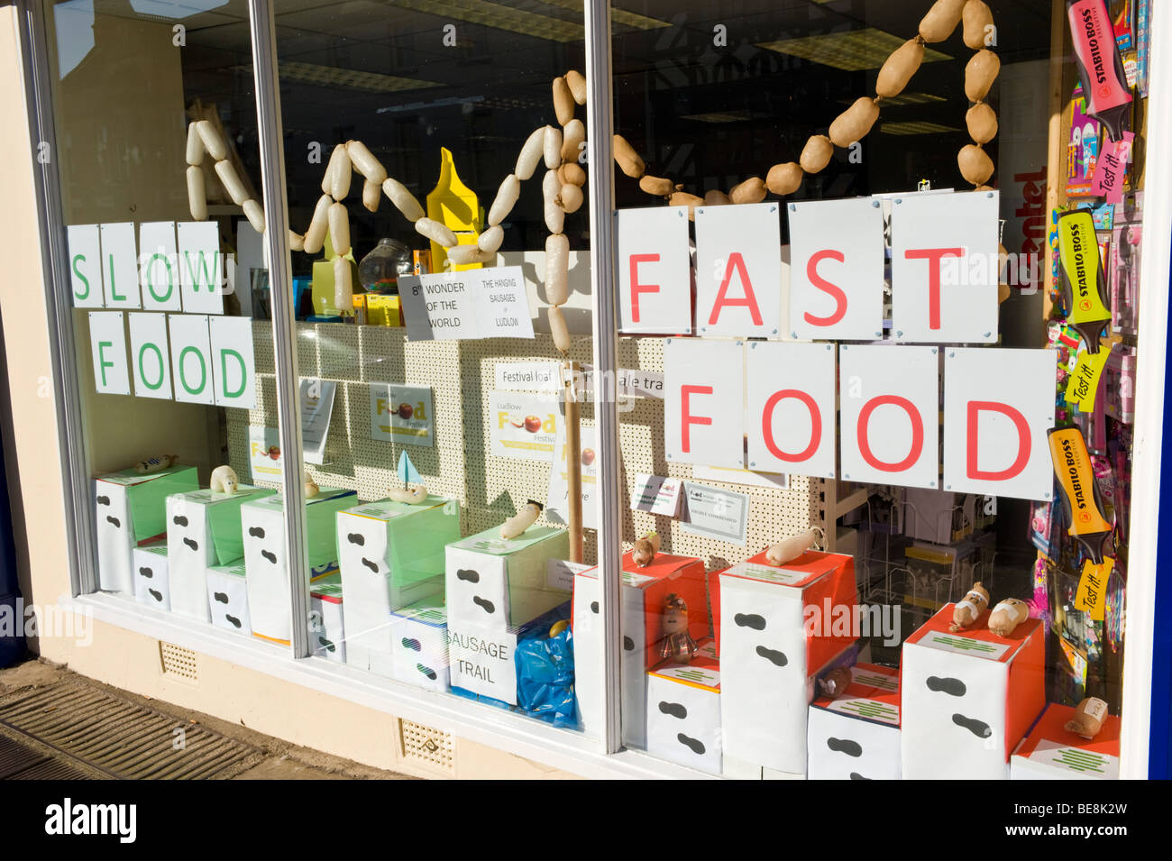 FAST FOOD SLOW FOOD display in window of stationary shop in Ludlow during the annual Food Festival Shropshire England - Stock Image