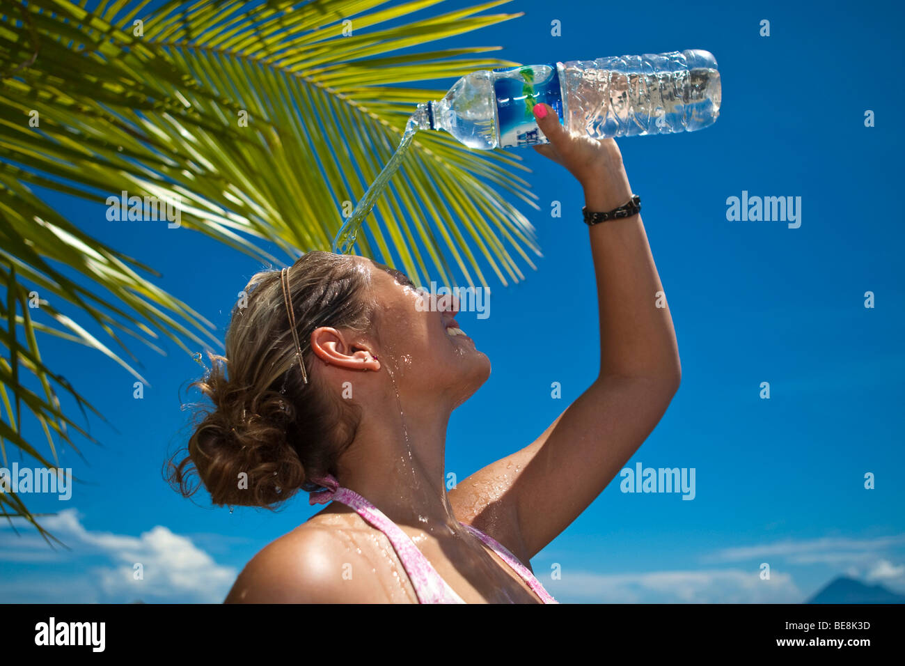Young woman on the beach pouring water from a water bottle over the head, Indonesia, South-East Asia - Stock Image
