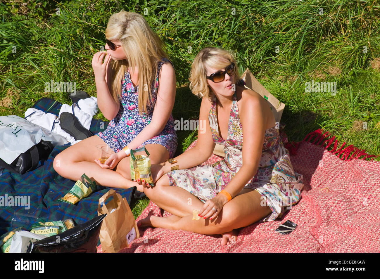Young women picnicking on grass in sunshine at Ludlow Food Festival Shropshire England UK - Stock Image